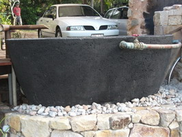 large outdoor bath, black scoria lava stone finish