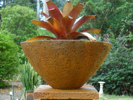 large garden planter bowl with plant on pedestal, iron verdi lava stone finish