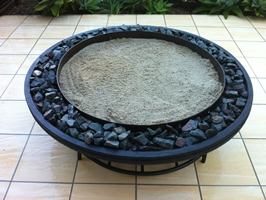 large japanese style fire pit on steel frame, black scoria lava stone finish, with lower wood rack